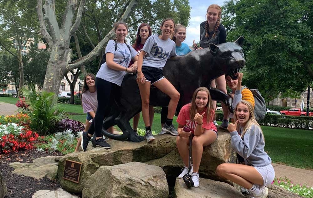 A group of campers gathered around a Pitt Panther as they have fun around campus
