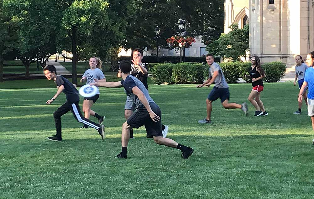 Students playing ultimate frisbee on the Cathedral lawn